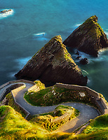 Dunquin Pier with offshore rocks and winding road. County Kerry, Ireland