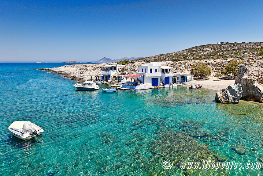 """Traditional fishermen houses with the impressive boat shelters, also known as """"syrmata"""" in Mytakas of Milos, Greece"""