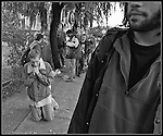 Homeless  and hungry people line up at the United Hamiliton Metodist Church near Haight Street, a person drops to his knees and prays, in  San Francisco, California.