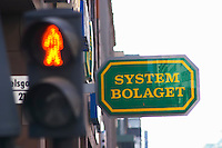 A neon sign for Systembolaget the Swedish monopoly for retail sales of alcohol behind a pedestrian crossing light with a red man indicating stop do not walk Stockholm, Sweden, Sverige, Europe