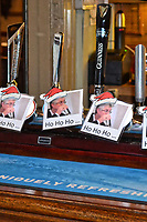 Pictured: Pictures of First Minister for Wales Mark Drakeford at the beer pumps of the King Arthur restaurant, in Reynoldston, Wales, UK.<br /> Re: A restaurant has stuck pictures of Wales' First Minister Mark Drakeford on its pumps at the bar and on a dart board, after recent changes to Covid-19 regulations, banned the serving of alcohol and all hospitality businesses closing at 6pm.<br /> The pictures at the King Arthur restaurant in Reynoldston in the Gower Peninsula, show the Welsh politician sipping water from a glass wearing a Santa hat which has been superimposed.