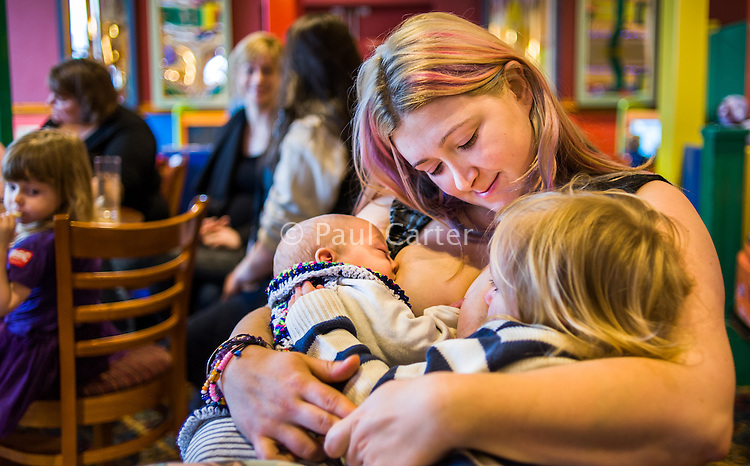 A mother tandem feeds her two children, one about twelve weeks old and one about 28 months old, at a sling meet held in the family restaurant and play area in a pub.<br /> Lancashire, England, UK<br /> <br /> Date Taken:<br /> 07-01-2015<br /> <br /> © Paul Carter / wdiip.co.uk
