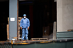 A health worker looks out of a loading dock as workers transport the bodies of Covid-19 victims into a temporary morgue at the Brooklyn Hospital Center in the Brooklyn borough of New York, the United States, Thursday, April 2, 2020.   Worldwide coronavirus cases have surpassed 1,000,000.  Photograph by Michael Nagle