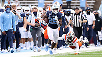 CHAPEL HILL, NC - OCTOBER 10: Javonte Williams #25 of North Carolina is chased by a diving Jermaine Waller #28 of Virginia Tech on a 29-yard run during a game between Virginia Tech and North Carolina at Kenan Memorial Stadium on October 10, 2020 in Chapel Hill, North Carolina.
