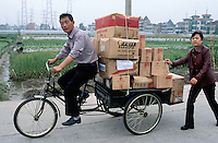 China. Province of Zhejiang. Hangzhou. Husband and wife. The man rides the delivery tricycle, fully loaded with carboard boxes (some containing electric components) while the woman pushes from the back. © 2004 Didier Ruef