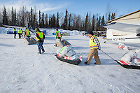 Volunteers move and hay, musher drop bags, people food and HEET to waitng Iditarod Air Force planes at the Willow, Alaska airport during the Food Flyout on Saturday, February 20, 2016.  Iditarod 2016