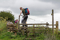 Cumbria, England, UK.  Hiker Traversing a Wooden Stile on the Hadrian's Wall Footpath.
