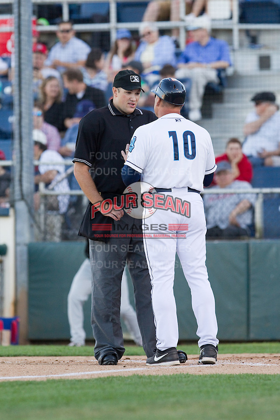 Home plate umpire Benjamin Bayer and Everett AquaSox manager Dave Valle discuss a call during a game against the Vancouver Canadians at Everett Memorial Stadium in Everett, Washington on July 9, 2014.  Everett defeated Vancouver 9-4.  (Ronnie Allen/Four Seam Images)