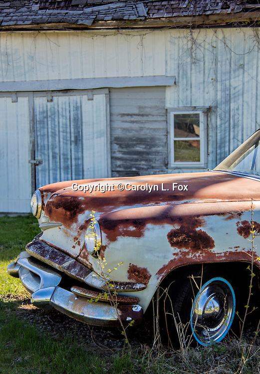 An old car sits by a barn in the country.