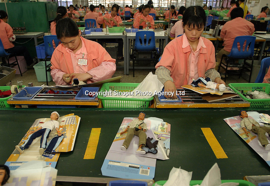 CAN0 20040226 GUANYAO, CHINA : Chinese workers assemble various dolls of the 'Barbie' division shown on the assembly line at the Mattel (H.K.) Ltd. plant in Guanyao, China on Thursday 26 February, 2004. Mattel is the largest toy maker in the world, and manufactures various products from Barbie to Hot Wheels in China.