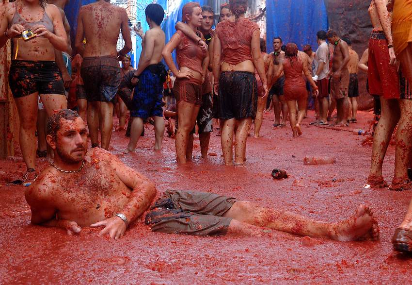 BUNYOL, SPAIN - AUGUST 31: A person having a rest immersed in tomato juice in the Tomatina August 31, 2005 in Bunyol, Valencia, Spain. Approximately 45,000 people pelted each other with a little over 100.000 kilograms of tomatoes. The tomatina is known as the world's largest tomato battle. Photo by Ander Gillenea