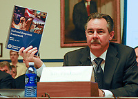 """Washington, DC, September 11, 2007 -- FEMA Administrator R. David Paulison holds up a copy of the National Response Framework at The House Transportation and Infrastructure, Subcommittee on Economic Delelopment, Public Buildings and Emergency Management hearing on """"Readiness in the Post Katrina and Post 9/11 World:  An Evaluation of the New National Response Framework"""".  FEMA/Bill Koplitz"""