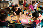 Education Preschool 4-5 year olds female teacher and children playing actively in classroom