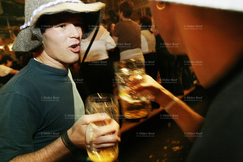 Switzerland. Canton Zürich. Winterthur. Oktoberfest. Bier fair. Cheers, Your health. Two young men are shaking their beer mugs. They both wear a hat on their head. Night life. © 2006 Didier Ruef