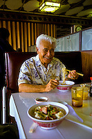 Hawaiian man in restaurant eating wo gau gee mein (dumplings, pork, shrimp, vegetables, noodles); Kaneohe, Windward Oahu