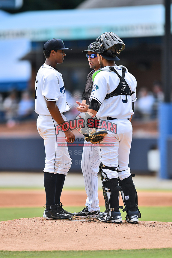 Asheville Tourists starting pitcher Erick Julio (29), catcher Joel Diaz (5) and pitching coach Doug Linton have a conversation on the mound during a game against the Augusta GreenJackets at McCormick Field on July 16, 2017 in Asheville, North Carolina. The GreenJackets defeated the Tourists 10-9. (Tony Farlow/Four Seam Images)