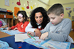 Sladjana Nedeljkovic, a Roma teacher at the Nasa Radost preschool in Smederevo, Serbia, helps a boy read. The children in this school are all Roma, and most are from families who came to the area as refugees from Kosovo. The school's work is supported by Church World Service.
