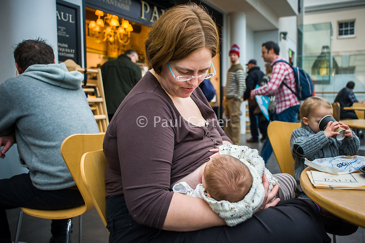 A mother looks at her baby as she breastfeeds in a museum cafe.<br /> <br /> London, England, UK<br /> 08/03/2015<br /> <br /> © Paul Carter / wdiip.co.uk