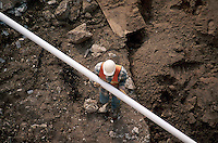Construction worker on job site laying PVC pipe.