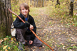 A young man hiking in the wood around Katherine Lake in Riding Mountain National Park, Manitoba, Canada.  Portraits of him with walking stick and binoculars.