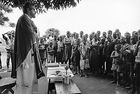 Uganda. West Nile. Okusijoni. Father Luigi of the Verona Fathers during a Sunday mass. A crowd of african families is attending the religious service taking place under a tree. The Comboni Missionaries of the Heart of Jesus, also known as the Comboni Missionaries of the Sacred Heart, the Verona Fathers, or the Sons of the Sacred Heart of Jesus, and originally called the Sacred Heart of Jesus is a male religious institute of papal law: the members of this congregation, known merely as Comboni, bear the letters MCCI. West Nile sub-region (previously known as West Nile Province and West Nile District) is a region in north-western Uganda. © 1989 Didier Ruef