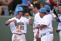 Beau Amaral #25 of the UCLA Bruins is greeted by teammates after scoring against the Oregon State Beavers at Jackie Robinson Stadium in Los Angeles,California on April 29, 2011. Photo by Larry Goren/Four Seam Images