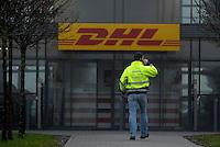"""DHL gab in einer Pressekonferenz am Dientsag (10.12.13) die Expansion am DHL-Hub Leipzig um eine weitere große Halle bekannt. Robert Viegers (Vors. der Geschäftsführung DHL Hub LEJ, Brille) zusammen mit Markus Otto ( Technischer Leiter und Vorsitzender der European Air Transport Leipzig GmbH / Vice President Aviation Germany ) erläuterte die Fertigstellung der Gebäude bis Ende 2014 - geplant ist das Schaffen von 400 Arbeitsplätzen - im Bild: Feature / Symbolfoto - DHL-Mitarbeiter (Techniker) mit Aufschrift """"DHL LEJ HUB Technical """"auf Jacke .geht zum Haupteingang. Logo . Foto: Norman Rembarz"""