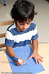 Education preschool 3-4 year olds art activity boy drawing with marker recognizable human figures vertical