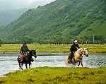 Chris and Rochelle riding across the Pasagshak River, Kodiak Island, Alaska