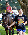 Southbury, CT- 14 June 2015-061415CM08- CL ONLY PLEASE Isabella Rodriguez, 7, of Oxford rides Daisy a Morgan horse, escorted by Christine Haddad, during the annual Southbury Strawberry Festival at the United Church of Christ in Southbury on Sunday.  The event featured homemade strawberry shortcake, chocolate-covered strawberries, barbecued food, activities for children, pony rides, live music and dancing.  Christopher Massa Republican-American