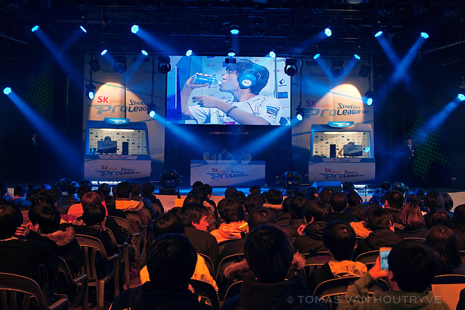 """Two cyber-athletes compete live on stage during a """"StarCraft"""" video game competition at the Yongsan E-Sports Stadium on Jan. 3, 2012 in Seoul, South Korea. The cyber-athletes can been seen in small cabins on each end of the stage. In the center is a panel of sports commentators. The image on the large center screen shows one of the cyber-athletes drinking water. The games are broadcast on TV in addition to the live audience."""