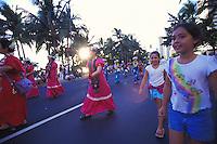 Girls watch Japanese women in hula muu muu's at the Pacific Asian Parade in Waikiki, Hawaii