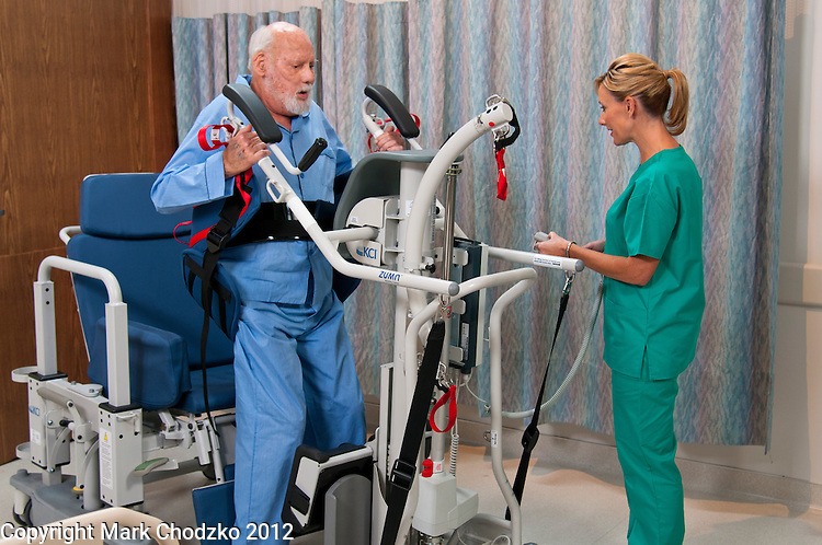 Healthcare professional helps patient stand using KCI device.