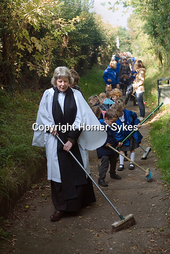 Old Mans Day Braughing Hertfordshire October 2nd. 2015. The vicar the Rev'd Julie Gawthrope sweeping Fleece Lane from the Fleece Inn leading to St Marys the Virgin church with the help of children from Jenyns First School.<br /> .