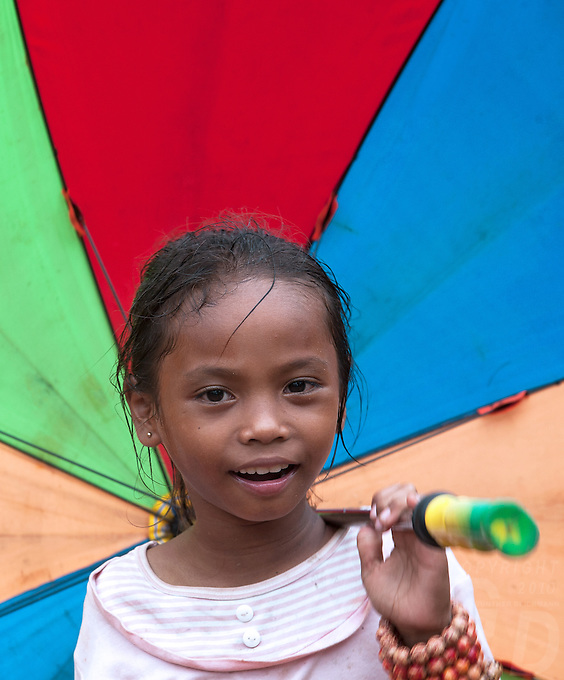 A girl with her umbrella, she is a local vendor selling souvenirs at one of the many temple ruins in the Siem Reap area. Cambodia