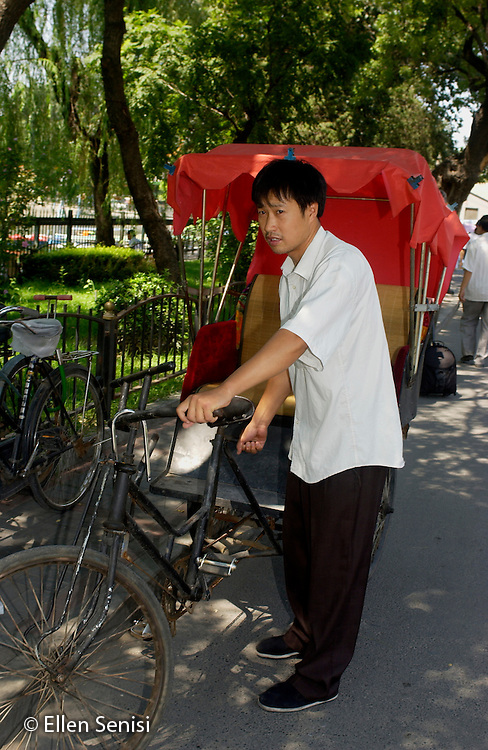 Beijing, China / August, 2004.Young man with his pedal cart / bicycle rickshaw / pedicab (a human-powered, common form of transportation in China) at a public park on Houhai Lake in northwest Beijing..©Ellen B. Senisi
