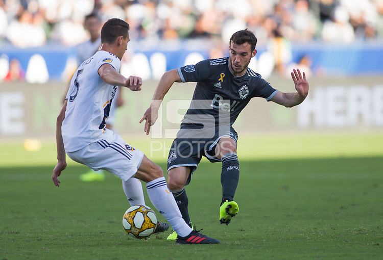 CARSON, CA - SEPTEMBER 29: Russell Teibert #31 of the Vancouver Whitecaps battles Daniel Stares #5 of the Los Angeles Galaxy for a ball during a game between Vancouver Whitecaps and Los Angeles Galaxy at Dignity Health Sports Park on September 29, 2019 in Carson, California.