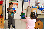 Education preschool 3-4 year olds boy and girl playing aiming toy guns made out of plastic interlocking blocks