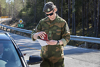 Krisitan Moen checking papers of travellers.  Norwegian authorites introduced strict measures to combat the Coronavirus (COVID-19) in March 2020. This included closing the borders, and any Norwegians returning from abroad is given two weeks quarantine. <br /> <br /> Police and soldiers from the Home Guard of the Army (Heimevernet) man checkpoints along side roads and regular border crossings to enforce the travel restrictions.<br /> <br /> <br /> <br /> ©Fredrik Naumann/Felix Features