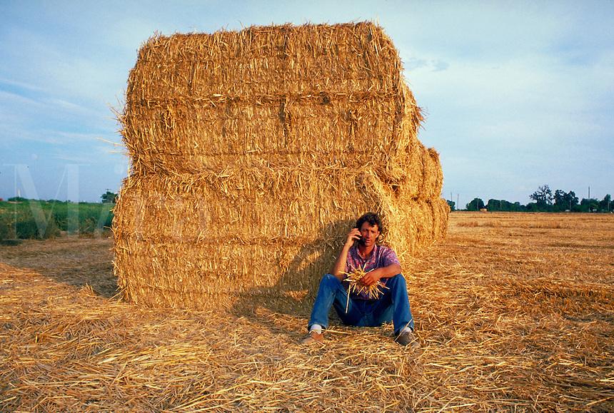 young farmer using cellular flip phone in straw field. farmer. California.