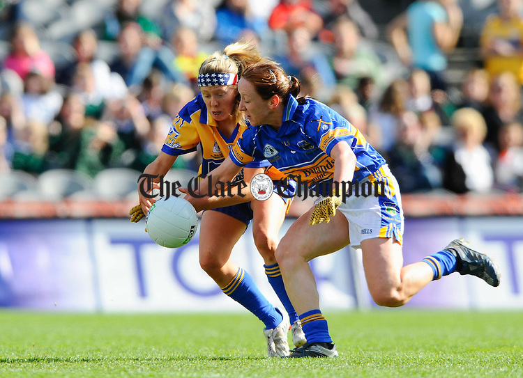 Clare's Aine Kelly is tackled by Maeve Corcoran during the Intermediate Ladies Football final at Croke Park. Photograph by John Kelly.