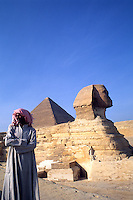 Close up of the famous Sphinx and the Pyramids of Giza in Egypt. Local Arab man portrait.