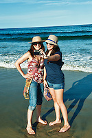 Women pose for vacation snapshot at the beach.