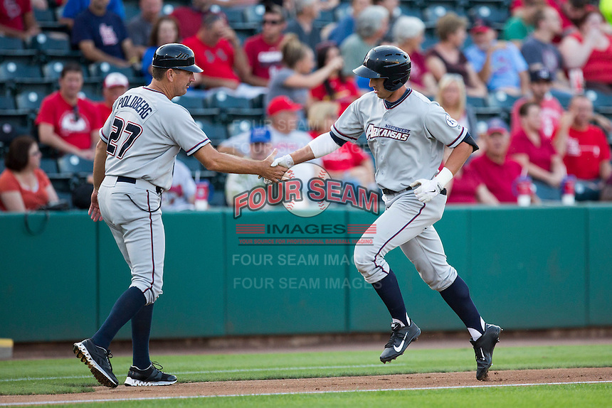 Lane Adams (8) of the Northwest Arkansas Naturals shakes hands with Brian Poldberg (27) as he rounds the bases after hitting a home run during a game against the Springfield Cardinals at Hammons Field on August 20, 2013 in Springfield, Missouri. (David Welker/Four Seam Images)
