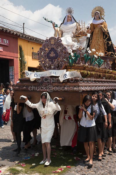 Antigua, Guatemala.  Semana Santa (Holy Week).  Women Carrying an Anda with the Virgin Mary on Top.  A man in a white tunic underneath the anda helps support its weight as the procession walks over an alfombra (carpet) of pine needles and flowers.