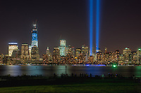 People observe and photograph the twin beams of light of the Tribute in Light, an annual memorial to the events of September 11, 2001, and the skyline of lower Manhattan from Liberty State Park in Jersey City, New Jersey on Tuesday, September 11, 2012.   This view of the skyline includes the Freedom Tower (One World Trade Center), under construction at the site of the original Twin Towers.  The Freedom Tower, lighted in the red, white, and blue colors of the American flag, is scheduled for completion in 2013.