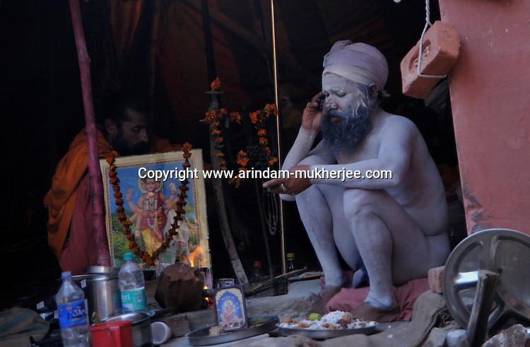 A Naga Sadhu (naked saint) using a mobile phone at Kumbh mela on 13th February 2010. Haridwar, Uttara Khand, India, Arindam Mukherjee