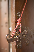 An old fashioned wrought iron latch handle held in place by a length of red cord