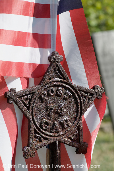 American Flag in a rusted star flag holder in a scenic New England cemetery during the summer months.