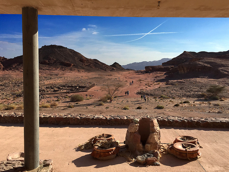 """23. """"Timna, the 'Copper Kingdom,' with ancient vessels, an """"X"""" and tiny figures in the distance"""":  Negev Desert.<br /> <br /> Timna is one of Israel's more than 60 national parks and nature reserves, an amazing number of sites for a country no bigger than New Jersey!<br /> <br /> At Timna, copper was mined more than 6,000 years ago, and continued to be mined periodically through the early Middle Ages.<br /> <br /> But for me, what's special about this image is the pairing of past and present. From the modern architecture of the visitor center, we see a desert without end, marked by an """"X"""" from contrails that create the illusion that planes have been flying on a crash collision course (just as Arabs and Jews may seem to be today). Broken clay vessels are chained to the concrete, and the tiny figures of the park's visitors traverse the ancient sands."""